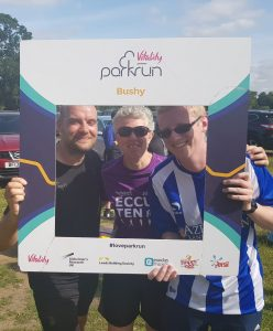 Phil, Kathryn and Stephen at Bushy parkrun holding the selfie frame with the parkrun logo and Bushy on it