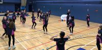 Group of school students warming up in a goalball lesson
