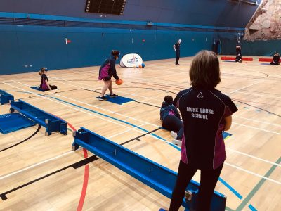 Action shot from Goalball UK School session in London, with goal judge in foreground