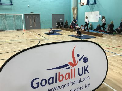 Photo with Goalball UK banner in foreground and school competition in background