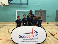 Smiling children with their gold medals from winning at the school competition, with GB player Caleb Nanevie supporting them