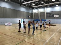 Group of school children playing 'over and under' at school transition event