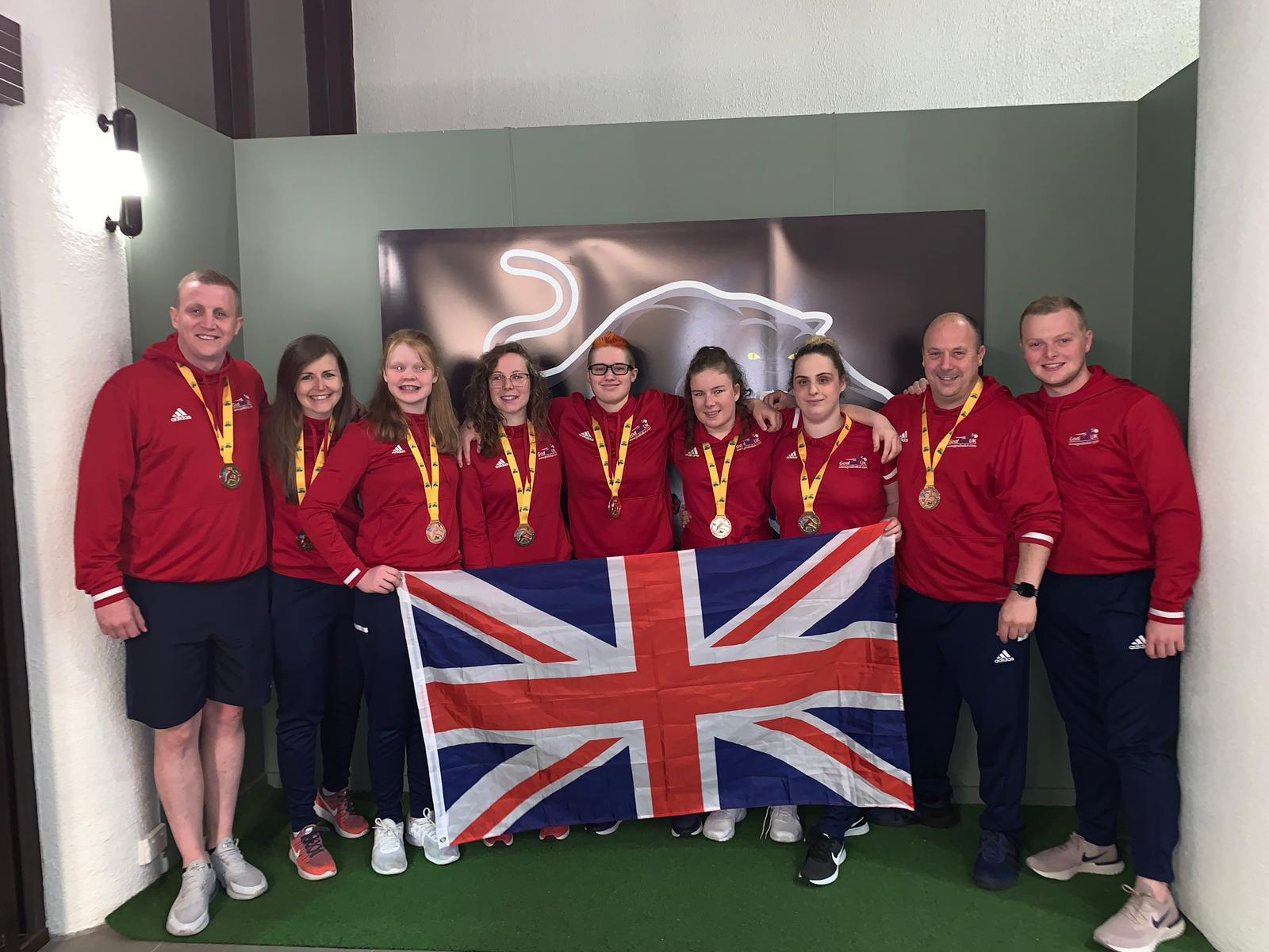 Group photo of GB Women under 19s with their bronze medals and holding the Union Flag