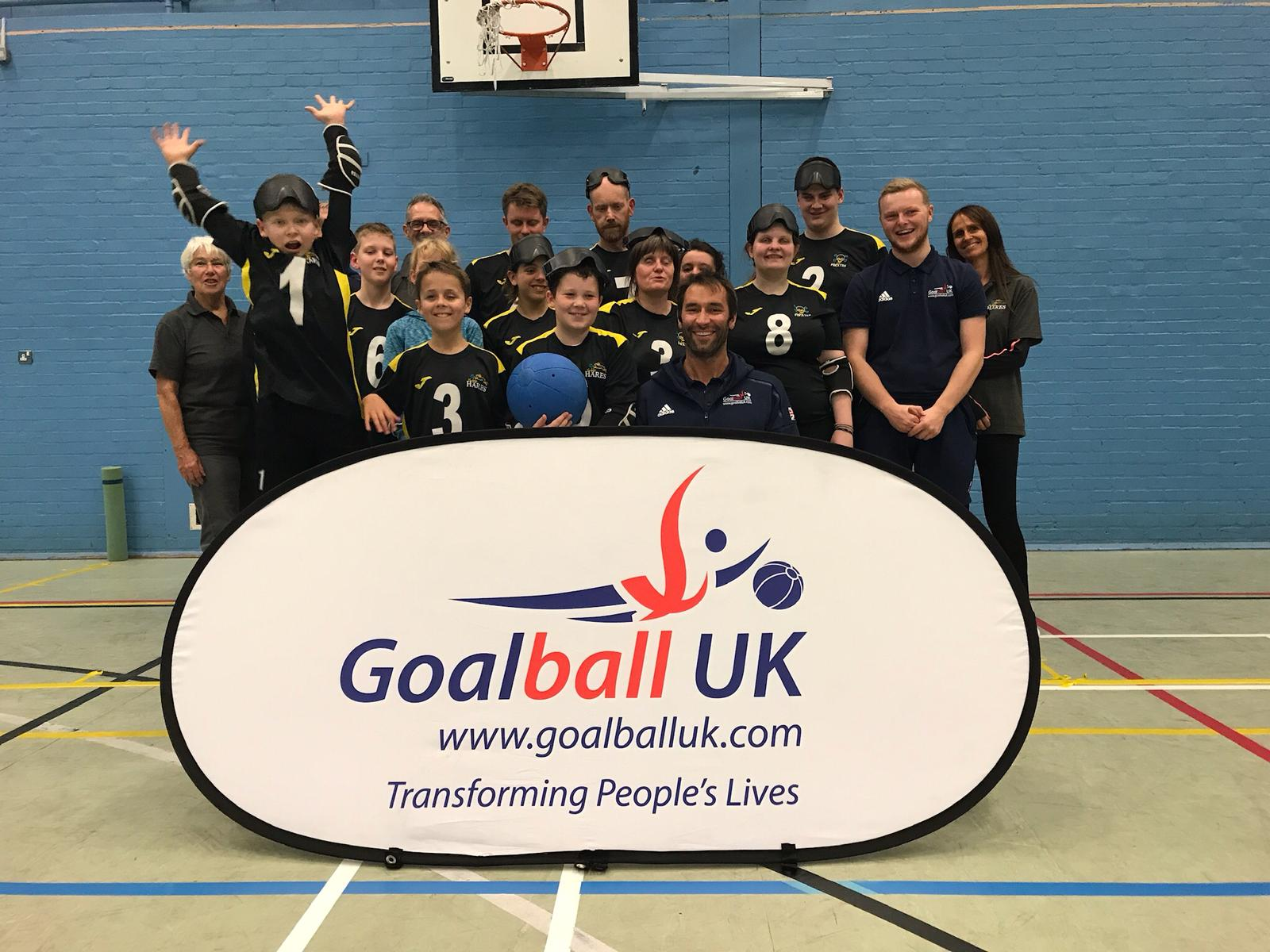 Group photo at Norwich Goalball Club with players and coaches, and Goalball UK staff Tom and Steve
