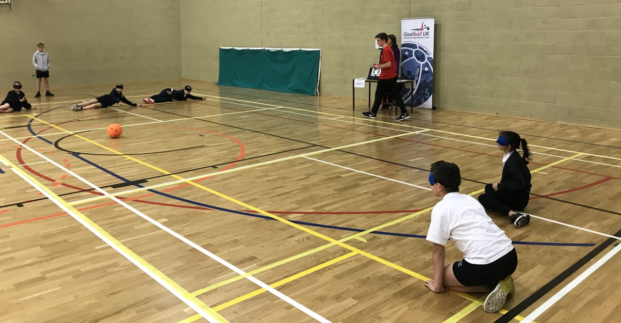 Action shot, with players on court, at a school goalball competition.