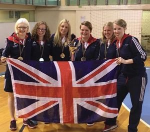 Women's Squad holding the Union Flag and wearing their gold medals.
