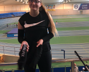 Sam smiling, and holding her eyeshades, with The EIS Sheffield in the backgorund