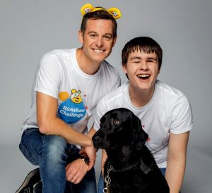 Goalballer Kelsey, smiling, with BBC presenter Matt Baker. Used in promotion of the 2019 Children in Need Rickshaw Challenge