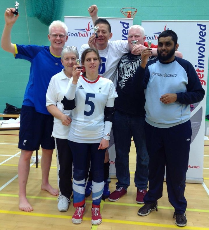 The winning team from the first pool holding their trophies