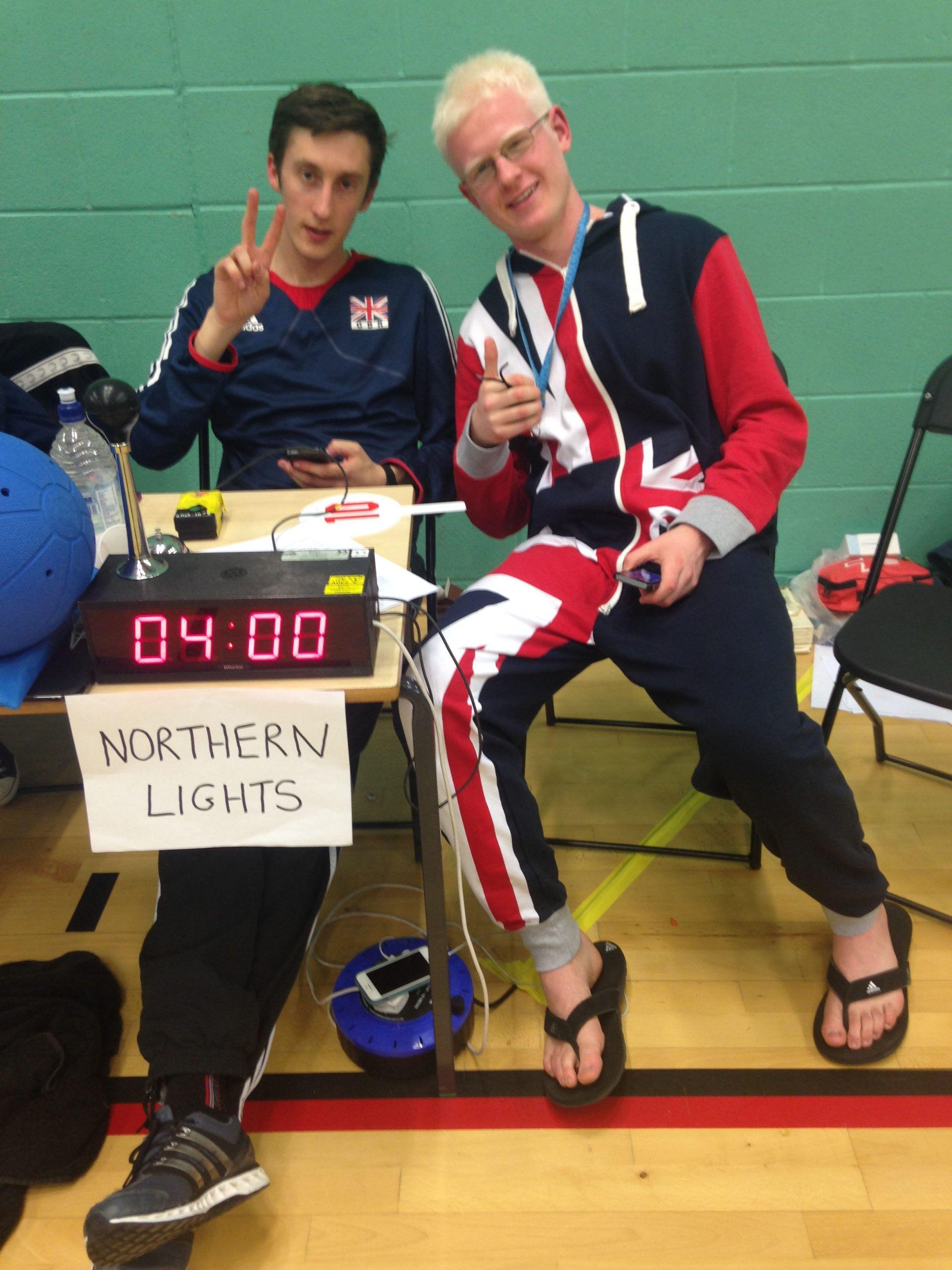 Alex Bunney and Adam Knott posing behind the officials table with Adam wearing a union jack one piece
