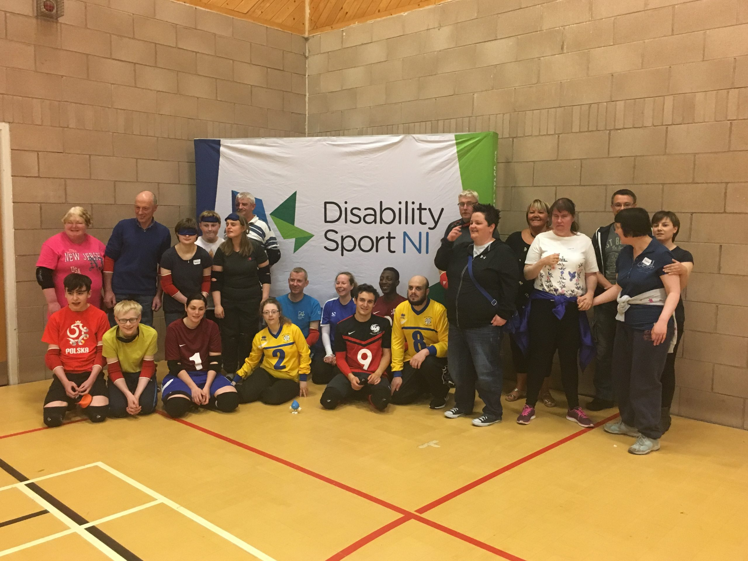 Group photo of everyone at the Norther Ireland Goalball Roadshow, with the Disability Sport Norther Ireland logo on a banner in the background