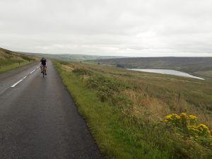 Phil cycling on a quiet road up in the Pennines