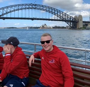 Tom Dobson smiling, with the Sydney Harbour Bridge and Opera House in the background