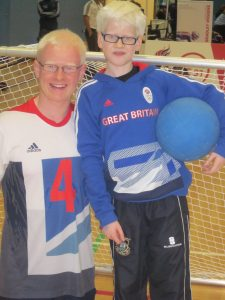 Image is of two goalball players in team GB kits posing for the camera