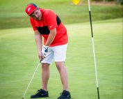 Image shows Nick playing golf, mid put