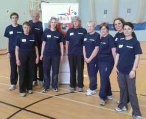 Image shows a selection of Goalball UK referees stood together, in front of the Goalball UK logo
