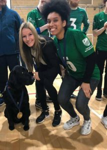 Aneesah and Coach Kirsty posing with a guide dog wearing a medal!