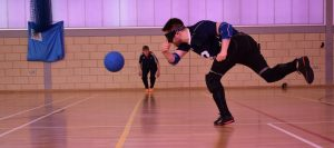 Image of a Winchester Goalball Club player throwing a ball at an elite tournament. Dina Murdie watching on.