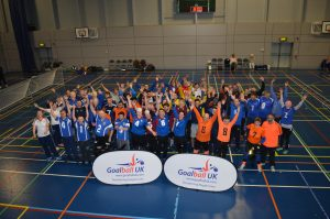 Post tournament photo with the teams in front of a banner putting their hands in the air.