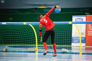 Caleb Nanevie playing for Great Britain in an international tournament. Caleb is about to throw the goalball.