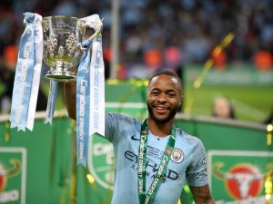 Raheem Sterling holding the Carabao Cup.