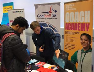 Alex Cockerham, at the time a Goalball UK activator, showing an interested student all things goalball.