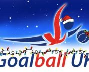 Goalball UK Xmas logo in front of a dark blue snowy background. The Goalball UK writing also has Christmas lights hung up across it.