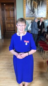 Dina Murdie wearing her British Empire Medal in a dark blue dress.