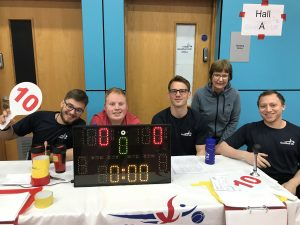 Volunteers at Sheffield North region tournament posing with smiley faces before a goalball game.