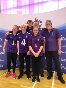Image shows Charlie stood with his Scarborough teammates in front of a Goalball UK banner