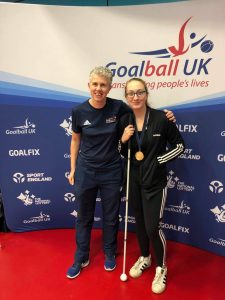 Samantha Gough and Kathryn Fielding stood together at a tournament in Sheffield in front of a Goalball UK banner.