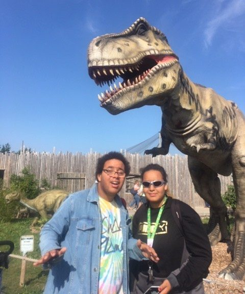 Image shows Alex stood with a friend infront of a T-Rex! Smiling at the camera!