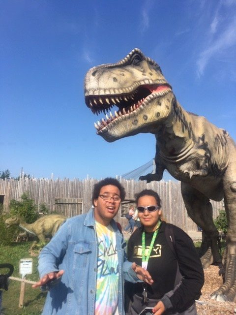 Image shows Alex stood with a friend in front of a T-Rex smiling at the camera!