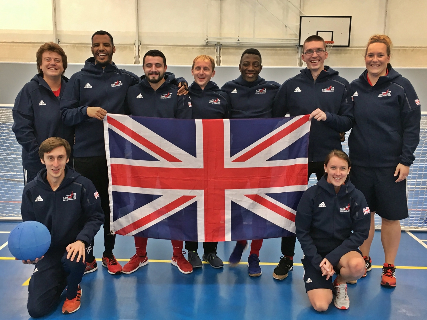 Image shows Faye (bottom right) with the 2017 GB Men's team holding the Union Jack flag