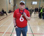 Image shows Joe Scott stood smiling at the camera, proudly holding his medal after a tournament!