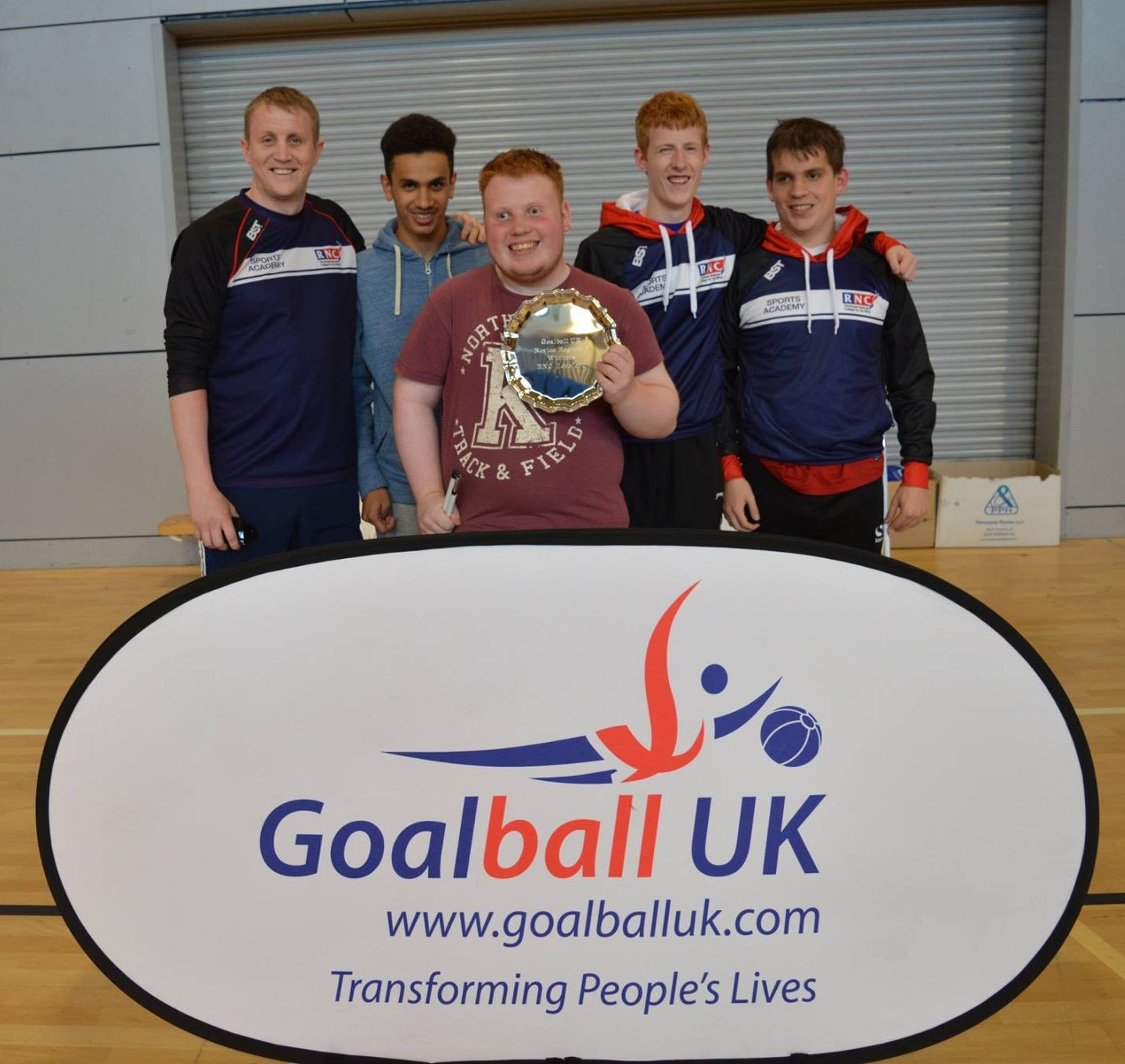 Image shows Ben stood holding a trophy along with members of the RNC goalball team. They are also stood with RNC and GB Womens coach Aaron Ford.