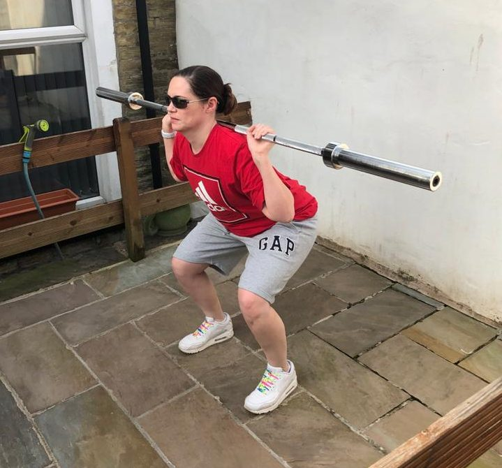 Image shows Gemma working out in her garden, she is part way through performing a squat