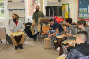 Young people and their parents taking part in a Drumming workshop at a Family Day