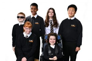 A group of NCW students, in school uniform, all smiling