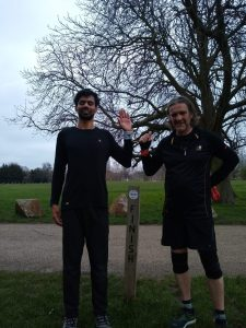 Naqi and his guide runner stood at the 5k finish line in the park