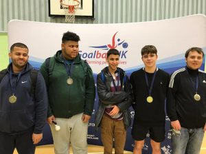 Image shows Abdul stood with his RNC academy teammates after a goalball tournament. They are all stood proudly with their medals in front of a Goalball UK banner.