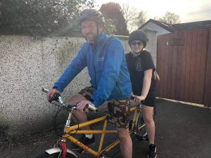 Sam and her dad on a tandem bike