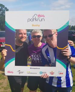 Phil Green, Kathryn Fielding and Stephen Newey standing together holding a park run sign.