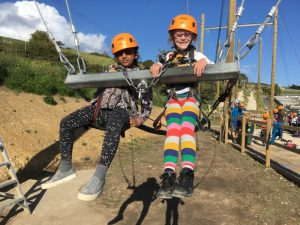 2 young girls with helmets and harnesses on taking part in an outdoor activity
