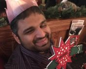 Image shows Bilal in a restaurant smiling holding up a Christmas cracker sign