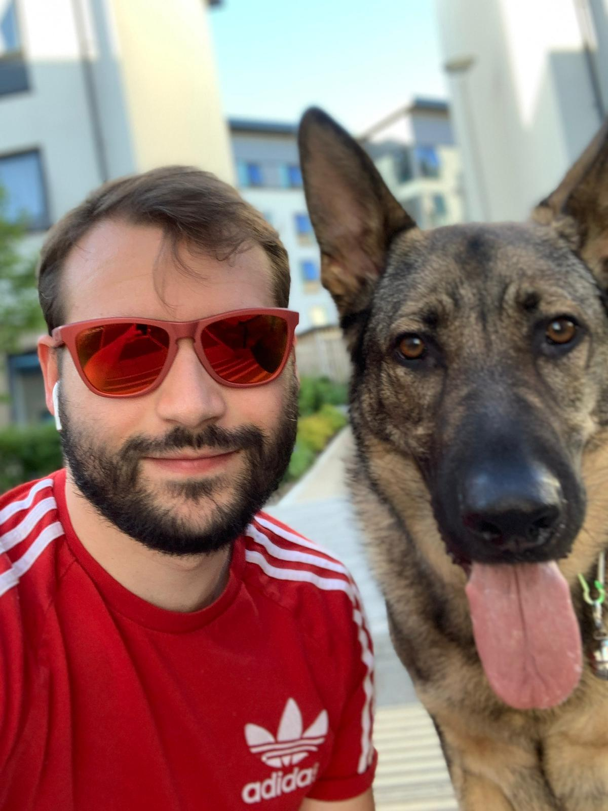 Image shows Dave Butler smiling at the camera with his guide dog, Alex