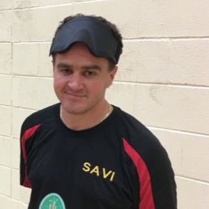 image shows Matt Cliff smiling at the camera after playing goalball with his eyeshades on his head