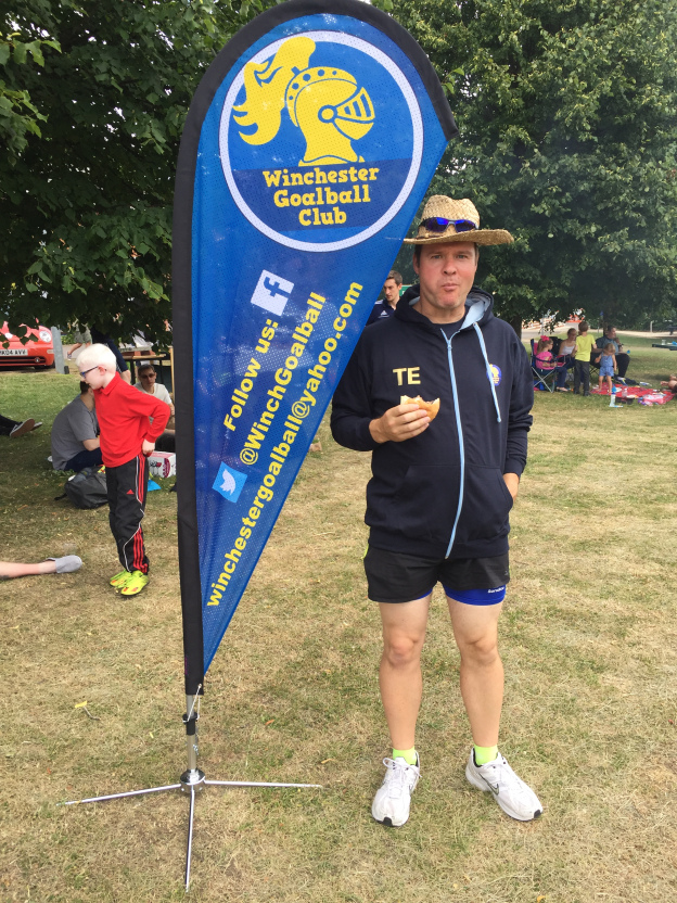 Image shows Tom Evison stood next to a Winchester Goalball Club banner with a burger at the 2017 Winchester BBQ