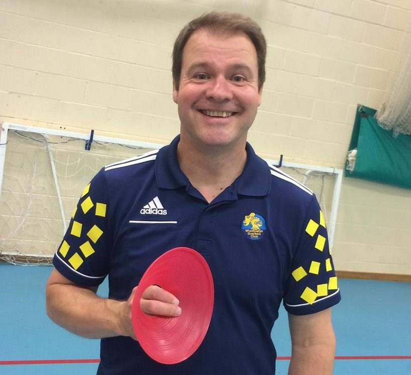 Image shows Tom Evison wearing his Winchester Goalball Club top, stood smiling at the camera and holding a red training cone