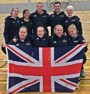 Group photo of GB Women and coaches holding the Union Flag